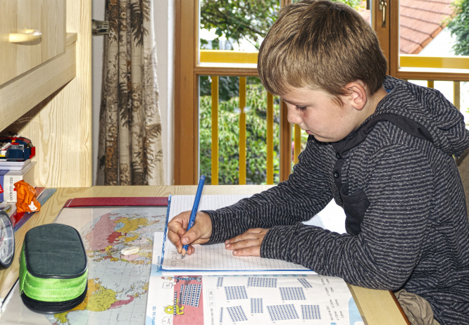 A young boy sitting at a table at home doing school work