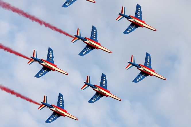 patrouille de france red white and blue planes fly past a blue sky