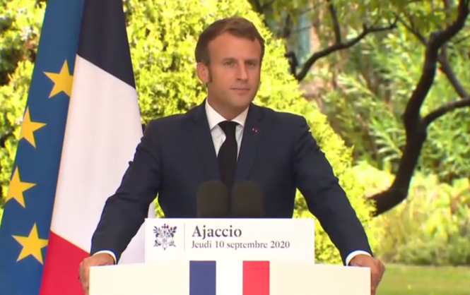 French president Emmanuel Macron standing at a lectern giving a speech in Ajaccio, Corsica