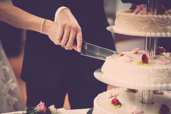 Wedding couple cutting cake. France Covid: Investigation opens into wedding with 200 guests