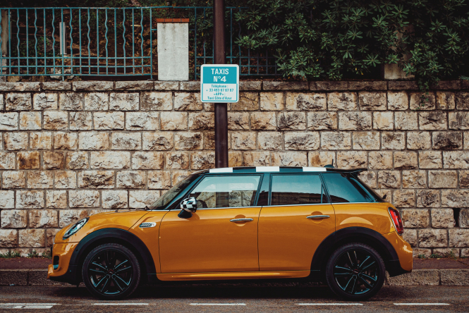 Orange mini parked outside the Hotel Belles Rives in Antibes, France.