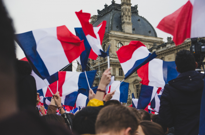 A crowd wave French flags at the Louvre, Paris, France.