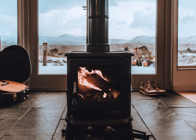 Black wood burner in a cosy room with a pair of shoes and a guitar on the floor. Who is eligible for a heat pump grant in France? Michael Shannon / Unsplash
