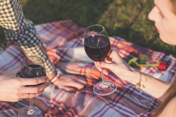 couple sit drinking red wine on picnic rug