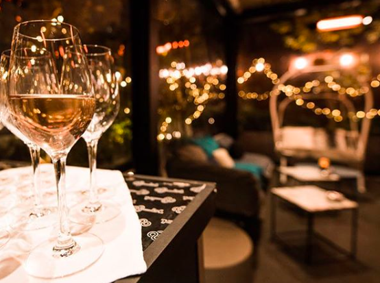 "Wine glasses in Le Terrass"" Hotel in Paris. French hotels are offering curfew 'nights out'."