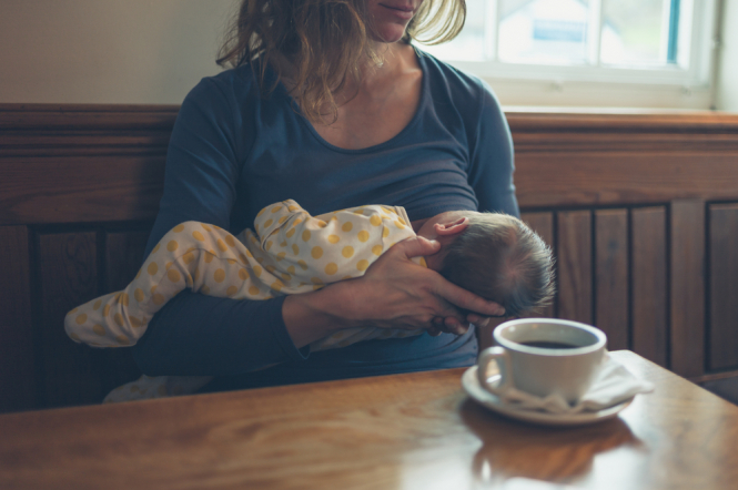 Woman breastfeeding baby in a cafe. French law proposed to protect women from abuse when breastfeeding