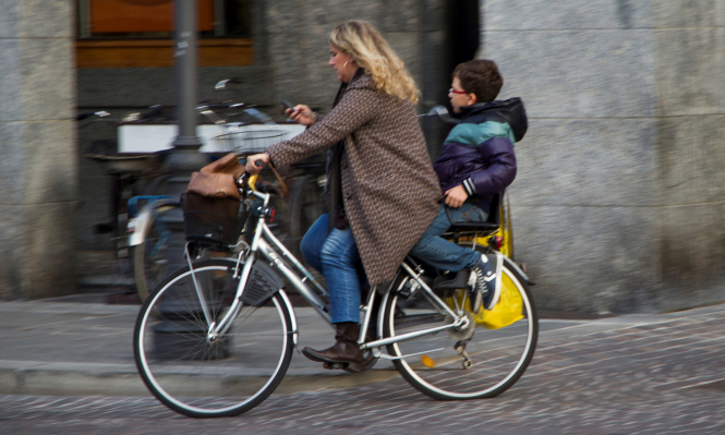 Woman cycling with youngster on back, both helmetless and woman is using mobile phone