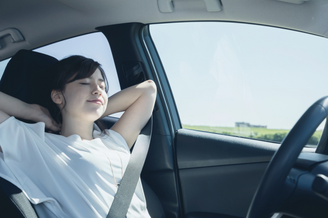 Woman relaxing in self-drive car. France first EU country to adapt its highway code for self-drive cars