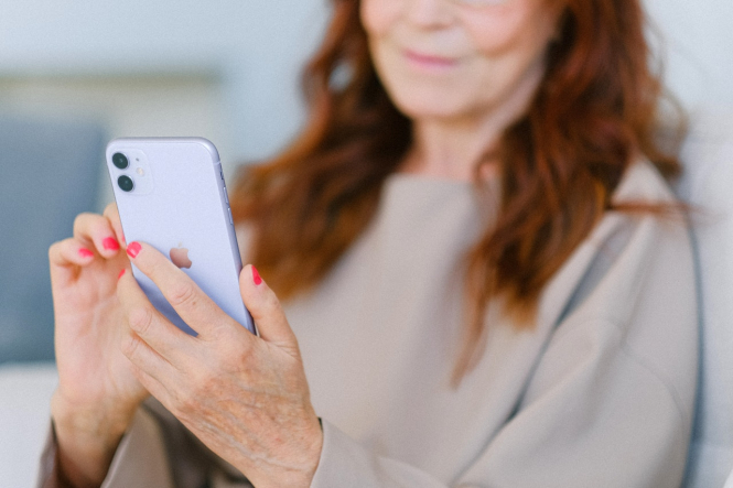A woman looking at a smartphone. Scam alert in France over malware texts about parcel deliveries