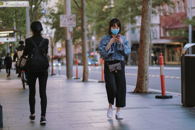 A woman wearing a mask walks down the street. Covid experts: France should end 'stop-start lockdowns' say scientists in new report