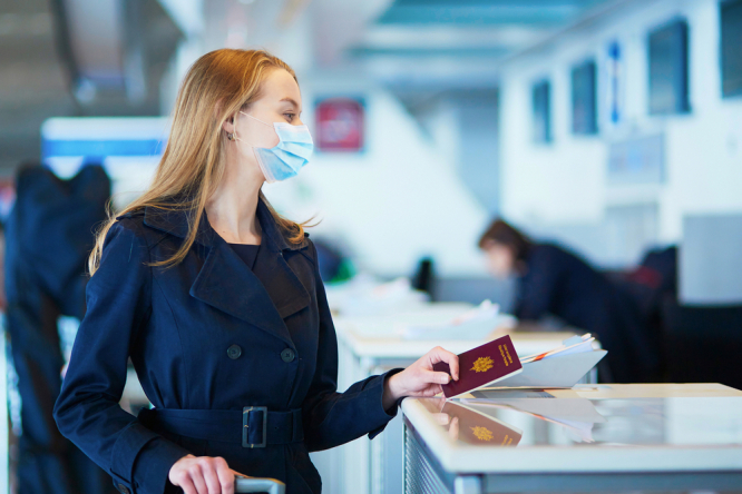 A woman at an airport wearing a mask