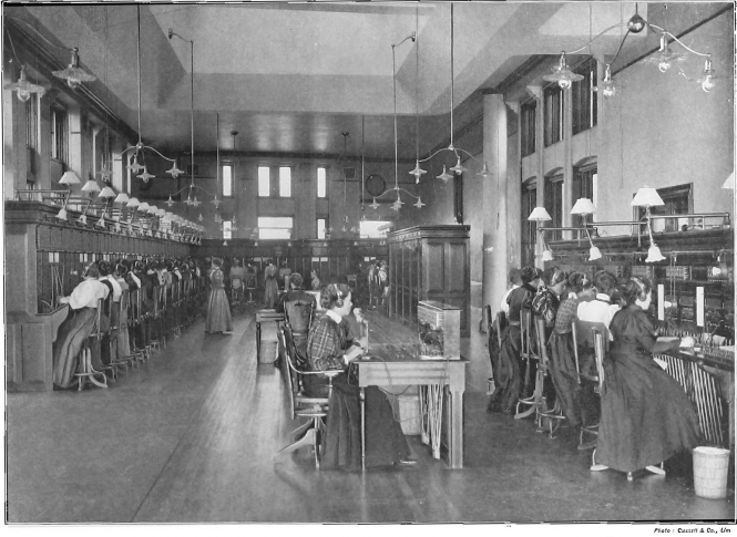 Black and white photo of women telephone operators in Montreal with desks disappearing into far background