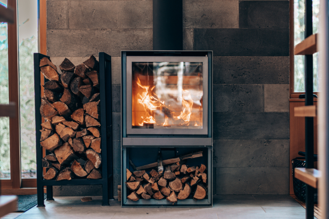 Wood-burning stove and a log pile. France plans to boost greener home wood burners with extra grants