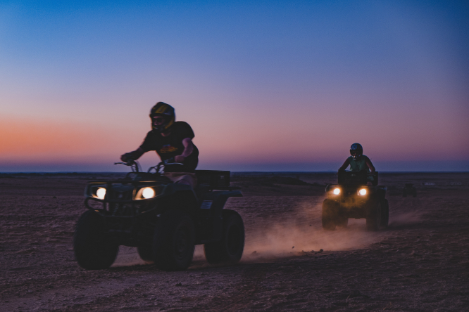 Your question answered: do I need insurance to use quad on my land? Pictured: quad bikers at sunset.