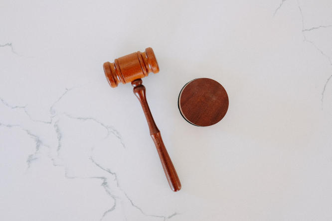 A wooden gavel on a white marble backdrop.