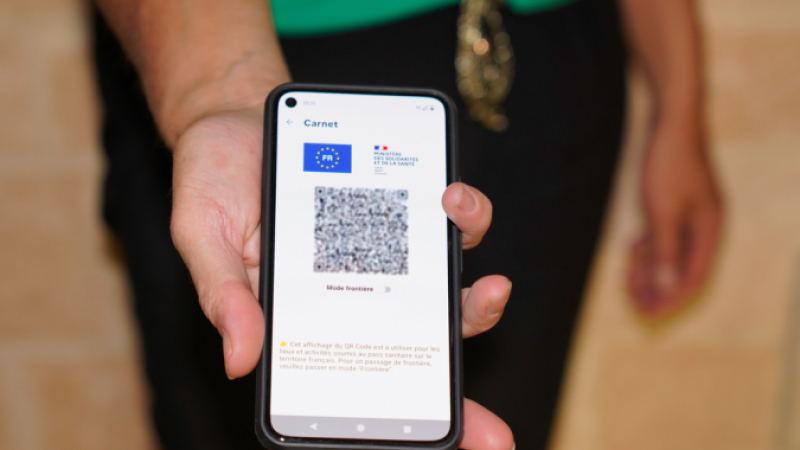 European health pass with QR code on a smartphone screen in hand