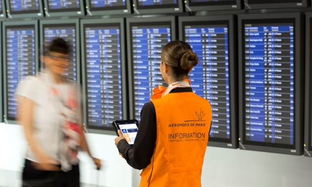 A Paris airport employee greets a passenger in front of an information board with flights listed