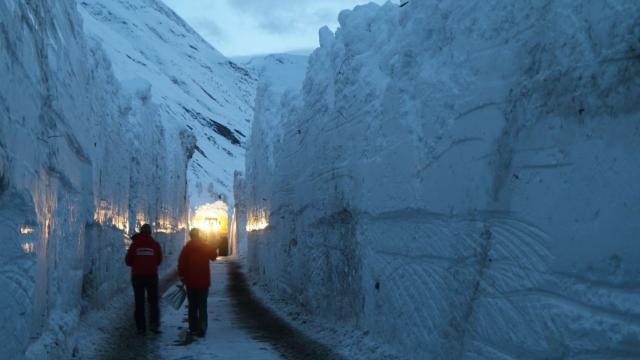 Two men dwarfed in corridor of snow on road after avalanche