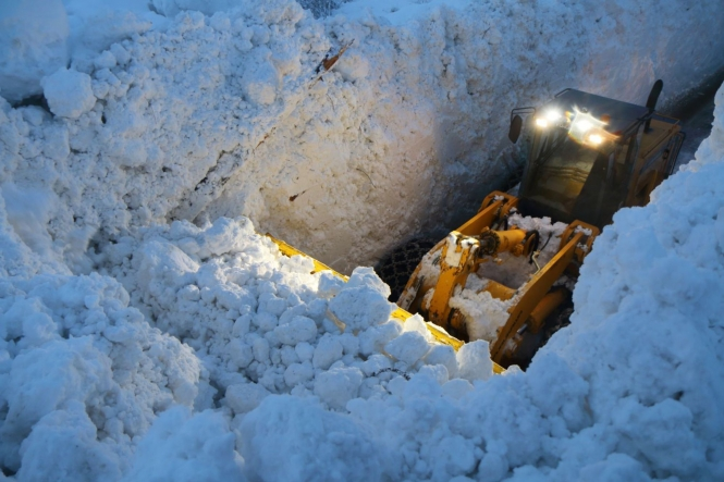 Digger deep in snow as it clears a road