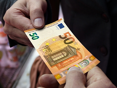 €50 note being exchanged between two hands