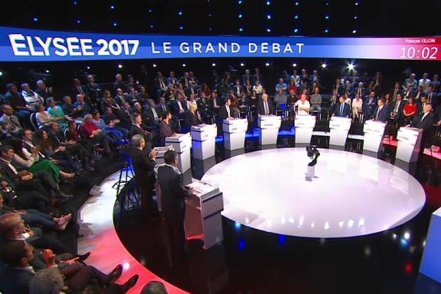 Audience watching debate of people in a semi-circle