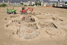 View of the caldarium baths at the Roman villa found at Langrolay-sur-Rance in Brittany with workers on dig site and digger plus houses in background
