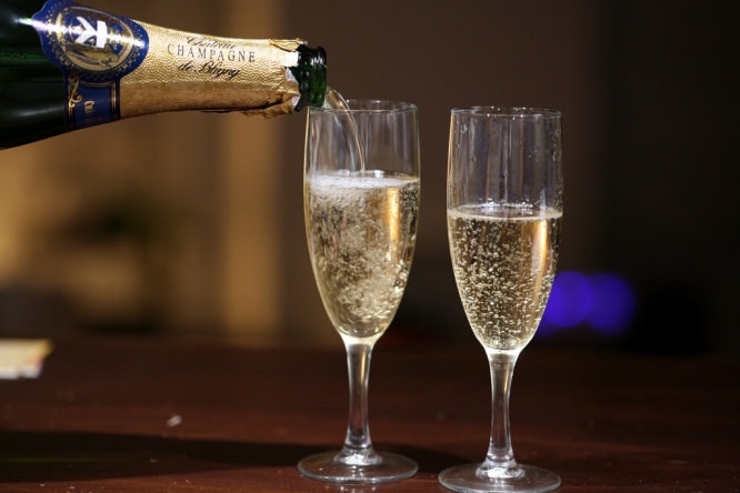Fizzy wine being poured into two flutes