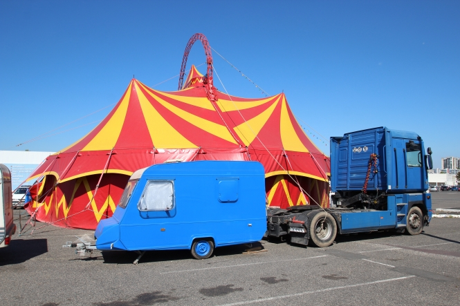 Red and orange circus tent with blue caravan and truck in foreground