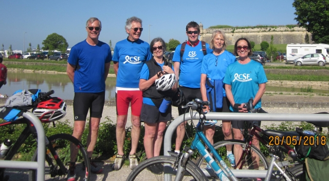 Six cyclists in blue tops with bicycles and the Canal du Midi behind them