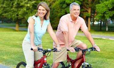 Couple cycle in short sleeves on red bikes on park path with trees in background to keep fit