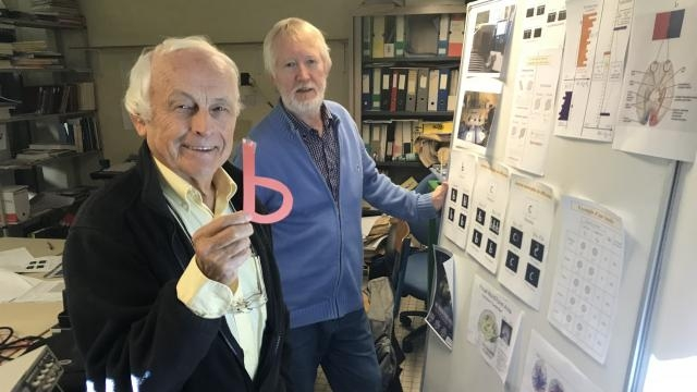 Two men in office or lab and one is holding up a letter 'b'