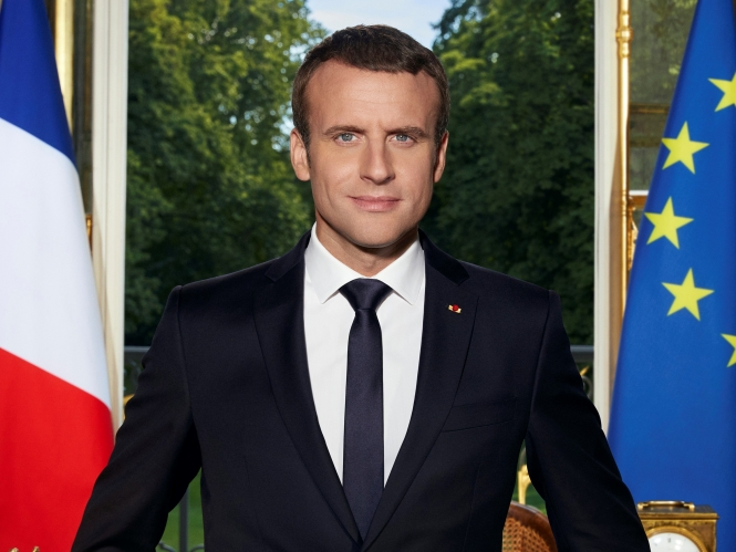 Emmanuel Macron with French and European flags and garden behind