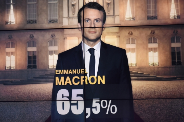 TV screen image of Emmanuel Macron with large 65.5% superimposed