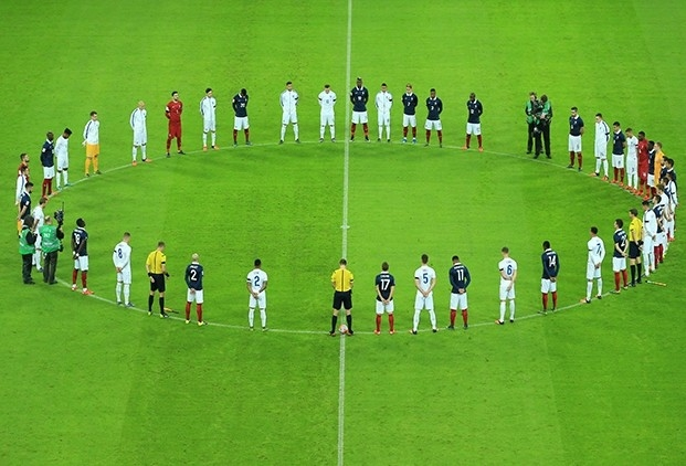 Players form circle on green pitch