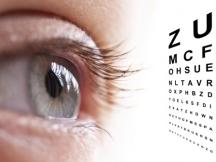 Large eye looks at eye test chart - called Echelle Monoyer in French