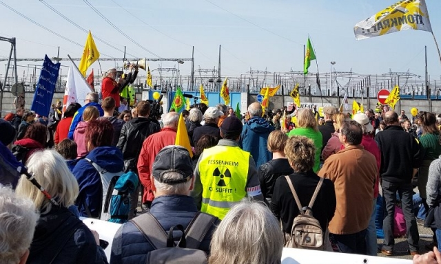 Crowd with flags in protest outside nuclear plant, one man wearing nuclear warning logo