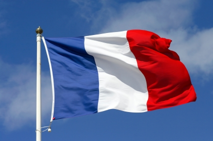 French flag against blue sky with clouds