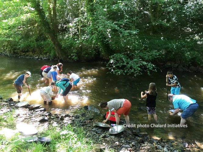 group of people bending over stream panning for gold
