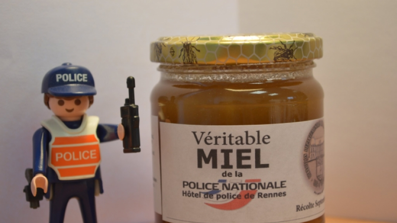 Small toy police figure next to jar of honey labelled police