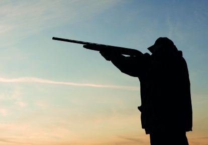 silhouette of hunter with gun raised on blue dusky sky