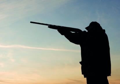 silhouette of hunter with gun raised on blue dusky sky