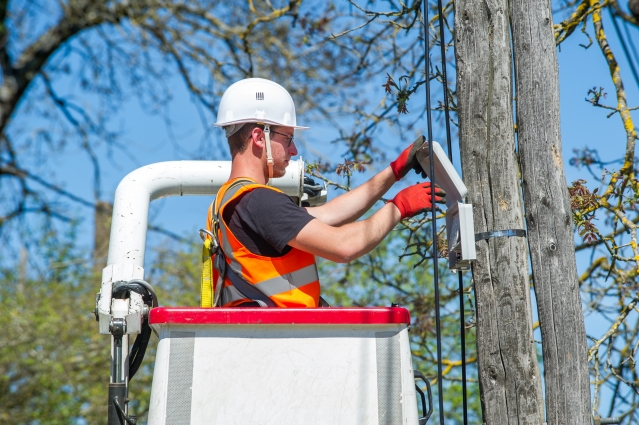 Man with safety helmet working on telegraph pole from a cherry picker