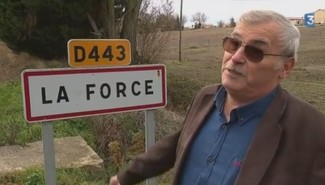 Man in front of French town sign La Force