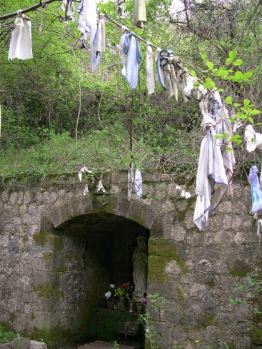 Holy well in wood with rags hanging from trees