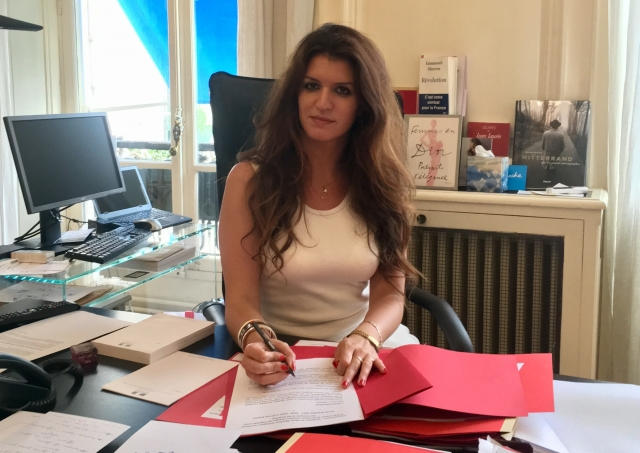 Woman signing papers in office with computer in background