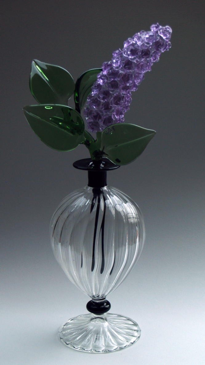 A delicate lilac-coloured glass flower and leaves in a clear vase