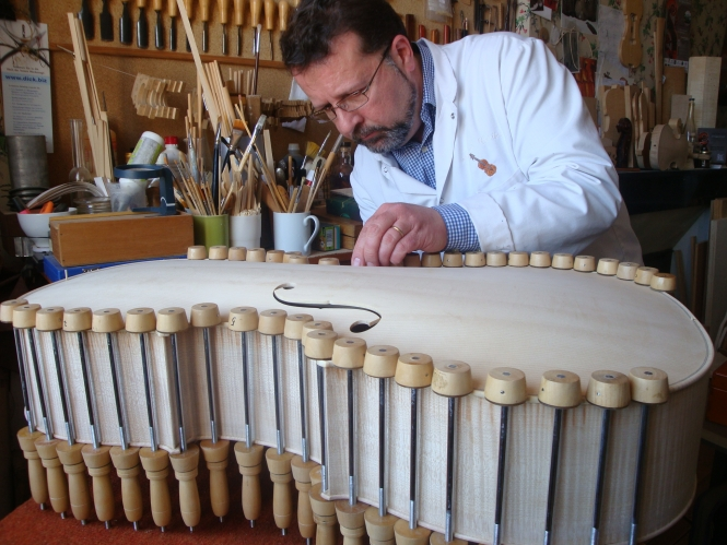 A man in white coat crafts a wooden instrument with a range of objects round the sides to maintain force