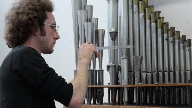 Man works on pipes of an organ