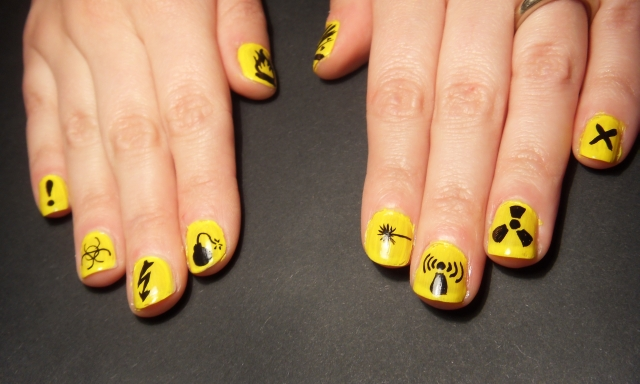 Funky nail varnish nail art with biohazard symbols in yellow and black on two hands