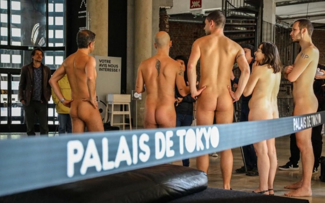 Mostly male naturists seen from rear at exhibition with banner from Palais de Tokyo
